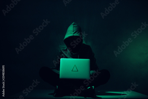 Fotografía toned picture of silhouette of hacker in hoodie using laptop
