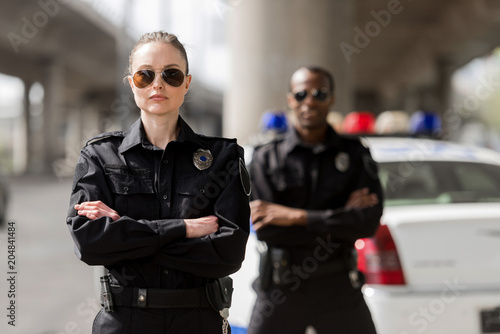 police officers with crossed arms looking at camera in front of car Fotobehang
