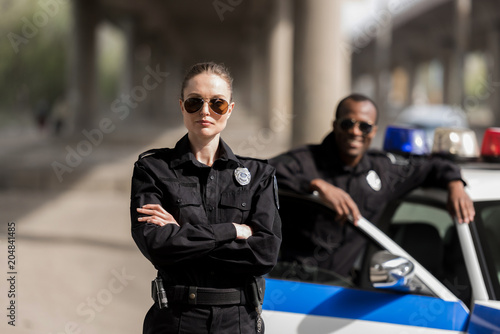 Fotografia, Obraz young serious policewoman standing with crossed arms while her partner standing