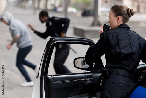 Photo policewoman talking by radio set while her partner chasing thief
