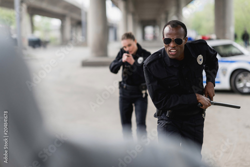 multiethnic police officers running for thief Canvas Print