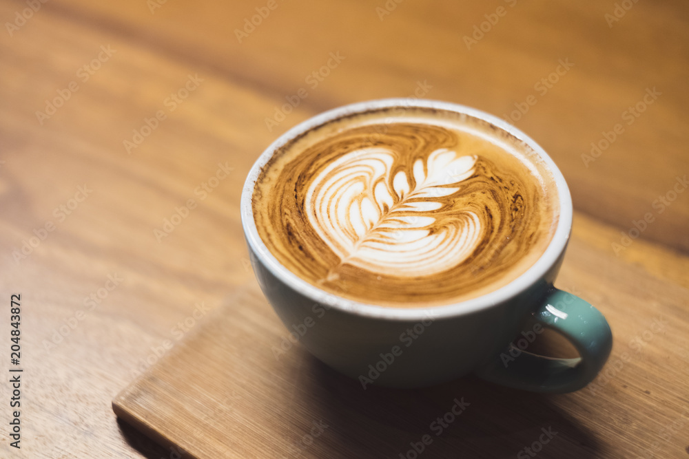 Close up hot cappuccino coffee cup with heart shape latte art on wood table at cafe,Drak tone filter,food and drink .