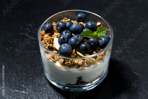 dessert with fresh blueberries, granola and cream on dark background