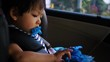 baby sitting on car seat with happy playing toy
