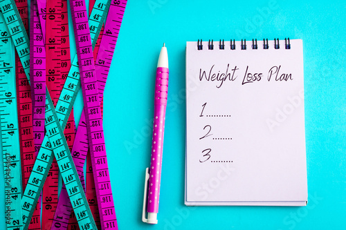 """Weight loss and Diet control concept background. Colorful of a Measuring tape on vibrant blue color background with blue book diary notepad and text as """" Weight Loss Plan """" for a healthy fitness ."""