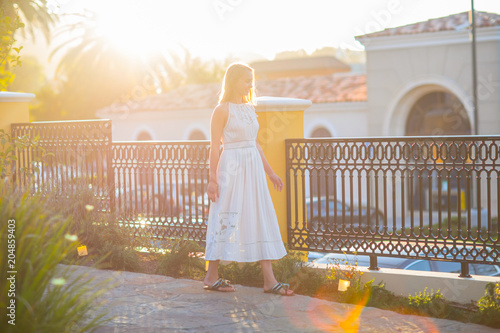 Spoed Foto op Canvas Natuur Romantic blong girl walking on the street in a beautiful sunset lights. Big copy space for a banner or message.