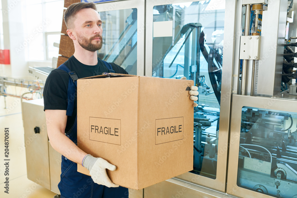 Fototapety, obrazy: Portrait shot of confident worker wearing overall and handling gloves carrying cardboard box and walking along spacious dairy factory warehouse