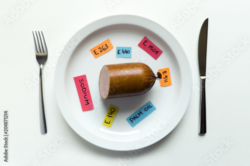 Colorful paper notes naming food additives and sausage on plate with fork and knife, food additive and unhealthy food concept.