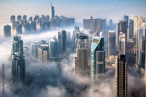 Dubai skyline, an impressive aerial top view of the city in Dubai Marina on a foggy day