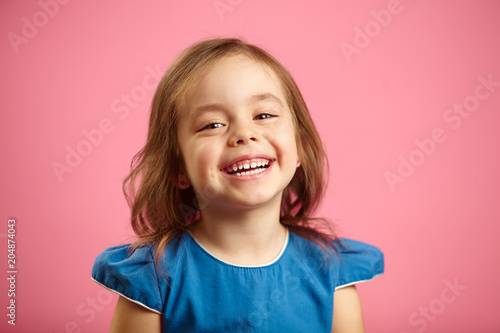 Fotografia  Cheerful little girl with charming smile and hearty laugh on pink isolated background, expresses heartfelt emotions of joy, is in a good mood
