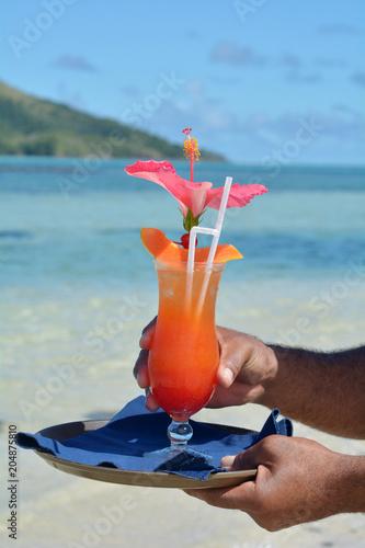 Keuken foto achterwand Cocktail Fijian waiter serving cocktail on a beach in Fiji