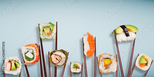 Poster Sushi bar Traditional japanese sushi pieces placed between chopsticks, separated on light blue pastel background.