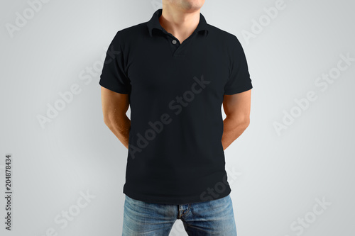 Mockup  black polo shirt on a strong guy. Isolated on a gray background.