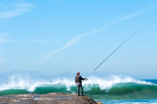 A Fisherman With A Fishing Rod On The Pier On A Background Of Ocean Waves
