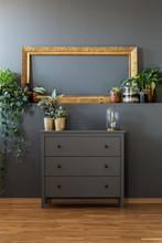 Golden Frame Above Gray Dresser