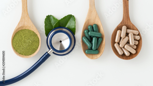 Herbal medicine with stethoscope on white background