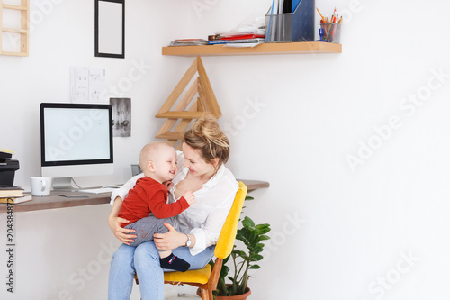 Cheerful young beautiful mother works freelance at home