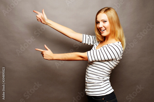 Poster  Happy smiling beautiful young woman showing copyspace, visual imaginary or somet