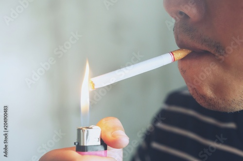 asian man smoking a cigarette  using lighter flame burn cigarette