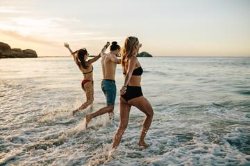 Fototapeta Friends holding hands and running at beach