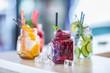 Various lemonades in mason jars with orange lime lemon otange strawberries and fresh fruit fruits
