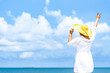 Back side of women wearing sunhat standing along the beach, looking forward to the beautiful blue sky. Travel and summer concept.