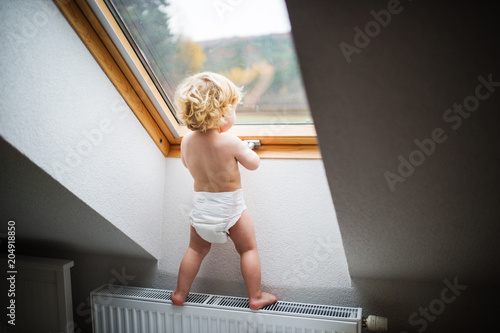 Toddler boy in a dangerous situation at home. Fototapet