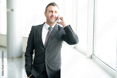 Fototapety, obrazy: Waist up portrait of successful businessman standing by window in office and speaking by phone smiling cheerfully, copy space