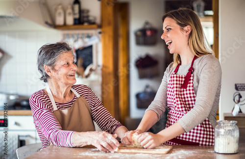 Fotografía  An elderly grandmother with an adult granddaughter at home, baking
