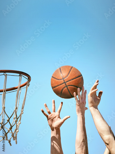 Fotobehang Bol Two basketball players throw the ball into the basket with both hands.