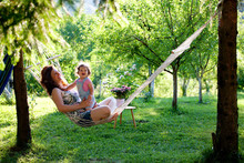 Happiness. Mother And Baby Girl In Hammock Smiling. Relaxing In Summer Garden. Family, Nature, People