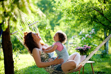 Joy. Mother And Baby Girl In Hammock  Relaxing In Summer Garden. Family, Happiness, Smiling,  Nature, People