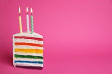 Slice Of Delicious Rainbow Cake With Candles On Color Background