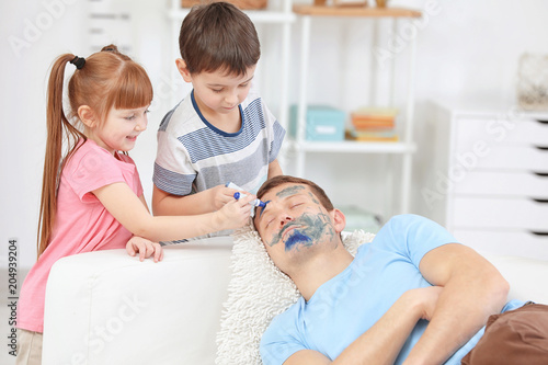 Fotografia Little children painting their father's face while he sleeping