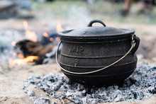 Cast Iron Pot Being Used To Cook A Camping Meal With Coals And A Wood Burning Camp Fire