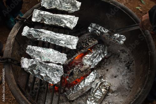 Fotografie, Obraz  Camping meals prepared in foil cook over a campfire