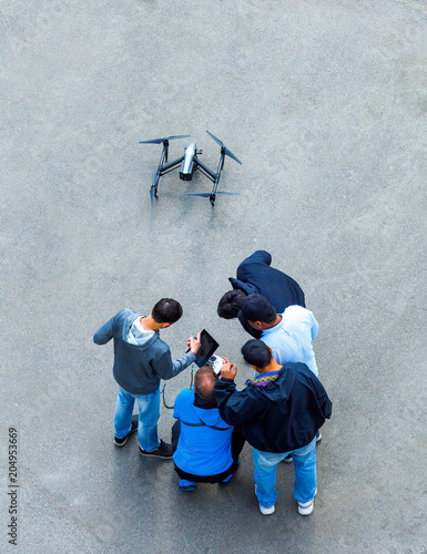 Fototapeta The unrecognizable person, camera operator and pilot with the controls panels teach to manage and use the drones of other new owners quadcopter UAV`s drone for commercial aerial photography