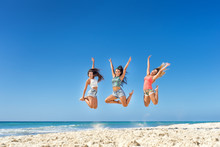 Happy Young Women Jumping At The Beach