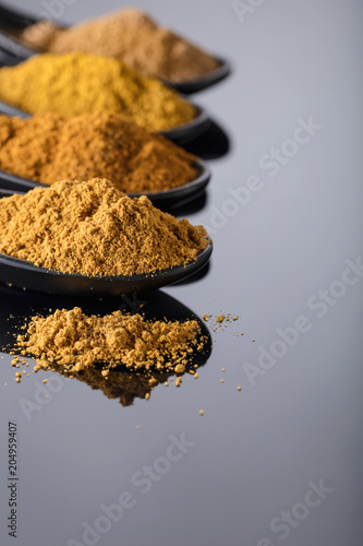 Foto op Canvas Aromatische Small black bowls of Indian spices on black reflective background .
