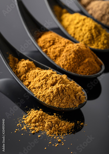 Foto op Canvas Aromatische Small black bowls of Indian spices on black background .