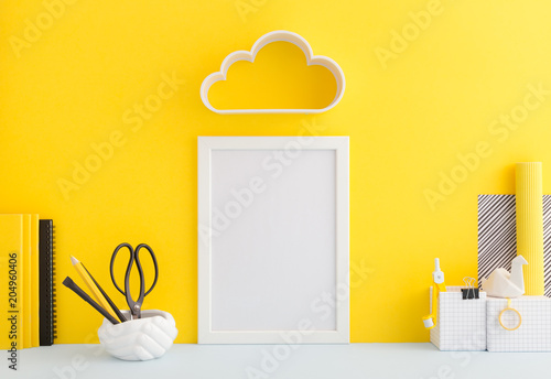 Fotografia  Creative desk  with yellow wall and supplies.