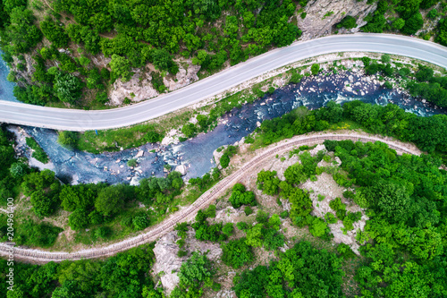 Foto op Canvas Groene Aerial view over mountain road and curves going through forest landscape