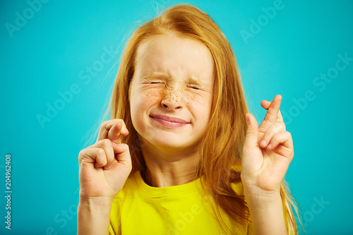 Fotomural Children girl tightly closed his eyes and put fingers crossed, make a wish, believe in the dream, expresses heartfelt emotions, has funny facial features, beautiful red hair with freckles