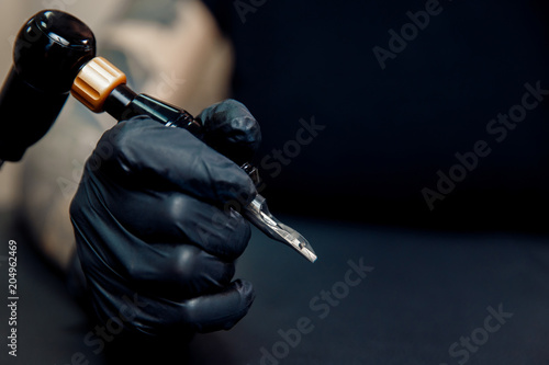 Woman master holding hand tattoo machine, preparing for drawing picture Canvas Print