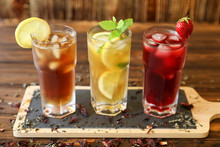 Three Glasses Of Different Cold Tea Drinks Black, Green With Lemon And Mint, Hibiscus Teas.