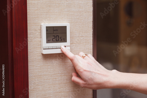 Photo  Woman switching a digital thermostat.