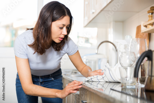 Poster  Young woman housewife cleaning furniture at  kitchen at home