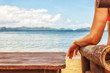 A girl sitting on a bamboo chair on the beach on a blue sea and sky background. place for text.