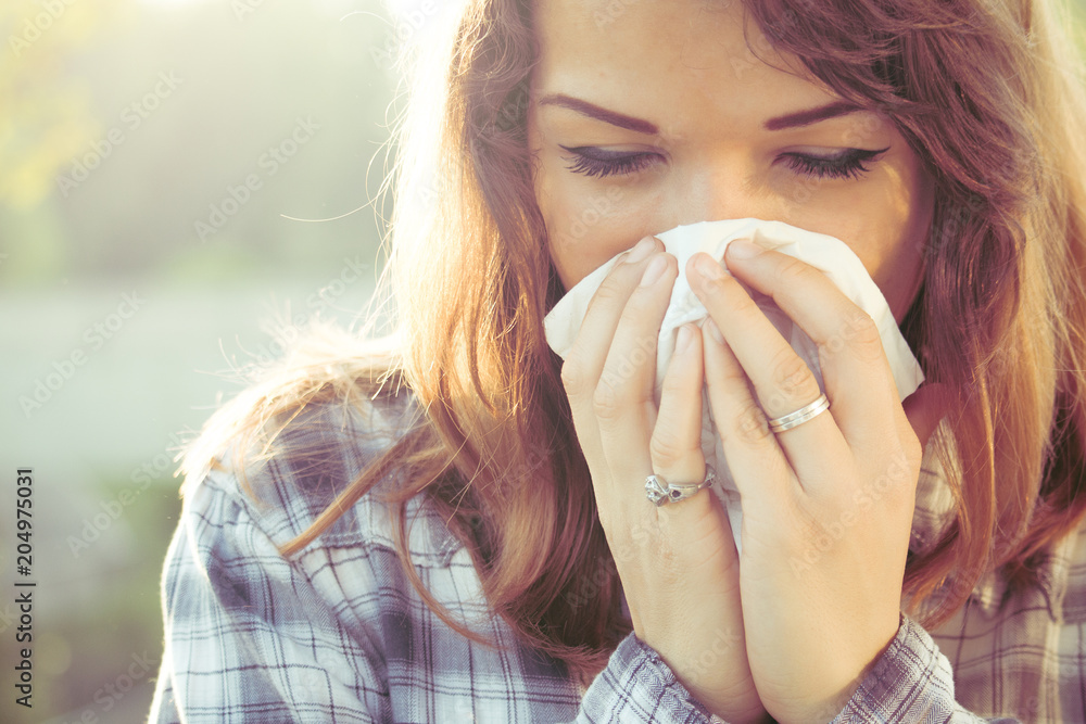 Fototapety, obrazy: influenza fever and pollen allergy. young woman blowing nose with paper tissue.