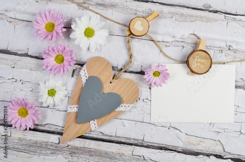 Pusta kartka na życzenia na tablicy drewnianej oraz serce i kwiaty - fototapety na wymiar
